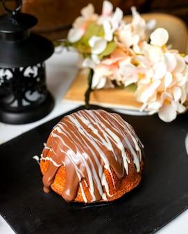 Zijaanzicht van cake met chocoladesaus op een houten raad