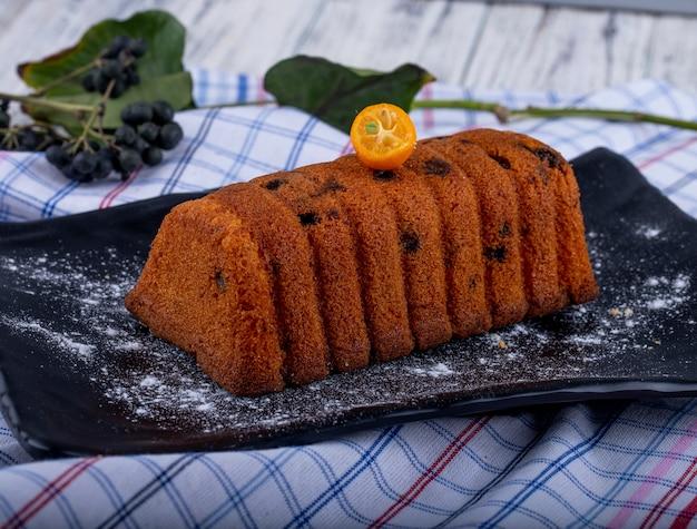 Zijaanzicht van cake met rozijnen versierd met kumquat segment en poedersuiker op een zwarte bord