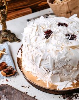 Zijaanzicht van cake versierd met witte chocoladestukjes op tafel