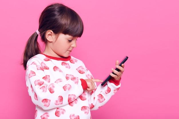 Zijaanzicht van charmante geconcentreerde kleine blogger die smartphone in handen houdt, vertoning bekijkt en iets typt, ruimte kopieert, poseren geïsoleerd over roze muur.