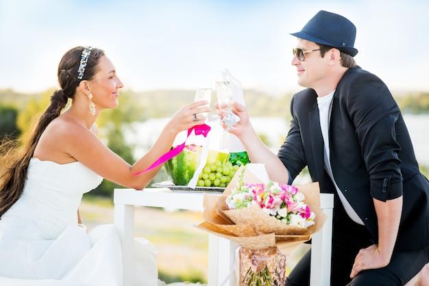 Zijaanzicht van charmante jonge paar bruid en bruidegom gerinkel glazen champagne zittend aan tafel met fruit en boeket bloemen