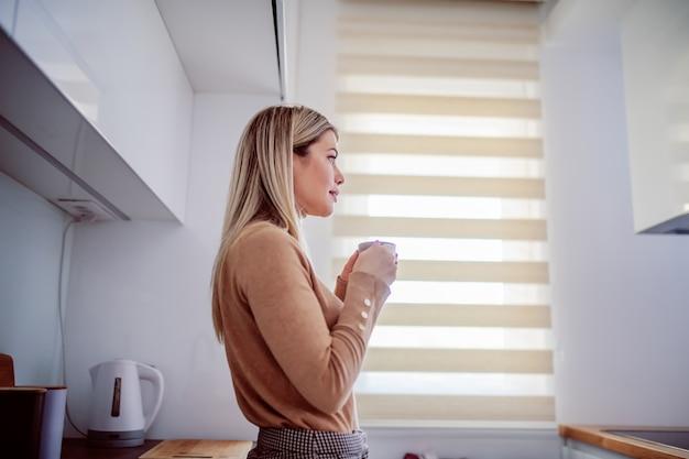 Zijaanzicht van charmante kaukasische blonde jonge vrouw leunend op het aanrecht en thuis genieten van koffie in de ochtend.