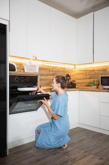 Zijaanzicht van charmante kaukasische krullende blonde vrouw in schort die uit oven gebakken voedsel nemen. binnenlandse keuken interieur. vrouw die bakplaat neemt. zelfgemaakte koken concept.