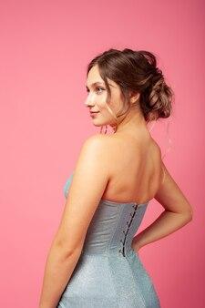 Zijaanzicht van charmante mooie vrouw in blauwe zilveren strakke jurk met vetersluiting op roze geïsoleerde achtergr...