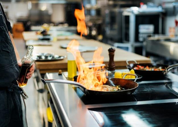 Zijaanzicht van chef-kok die een schotel in de keuken flambeing