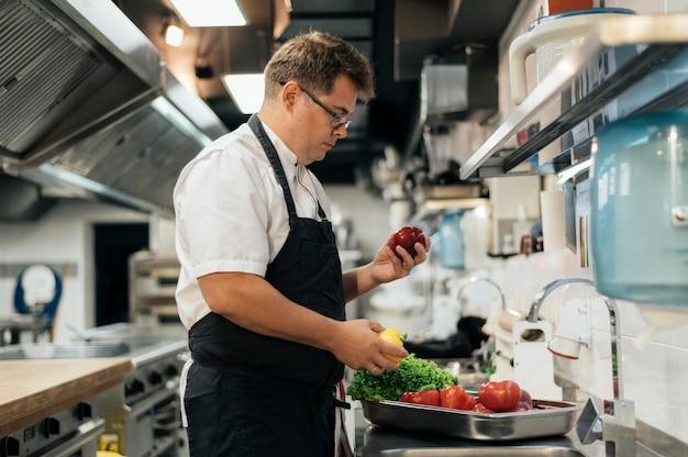 Zijaanzicht van chef-kok die met schort groenten in de keuken controleert