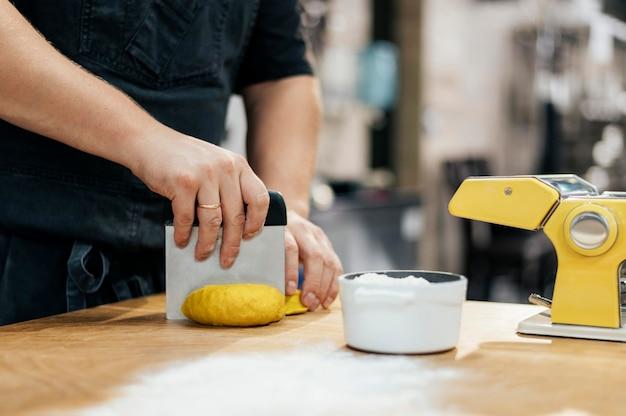 Zijaanzicht van chef-kok met schort die deegwaren snijden