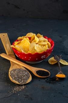 Zijaanzicht van chips in kom en houten lepels met zwarte zaden op zwart