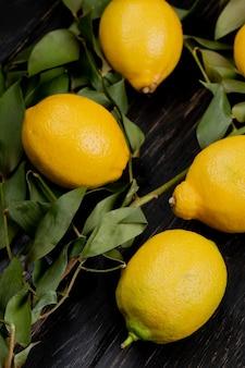 Zijaanzicht van citroenen op houten achtergrond die met bladeren wordt verfraaid