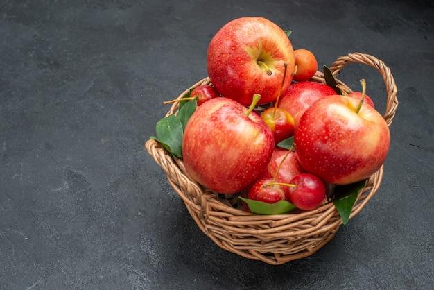 Zijaanzicht van close-up fruitmand van de smakelijke appels en kersen