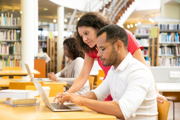 Zijaanzicht van collega's die met laptop bij bibliotheek werken