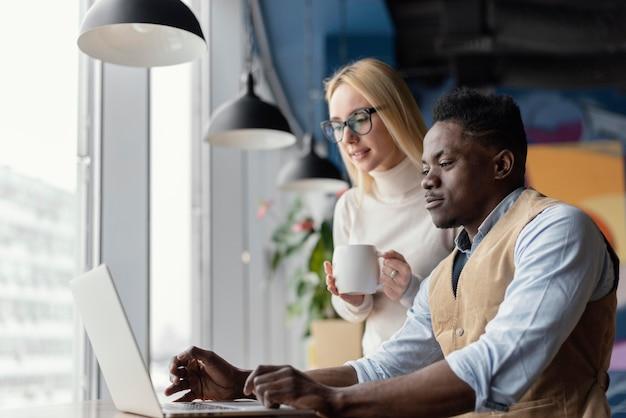 Zijaanzicht van collega's op kantoor die met laptop werken
