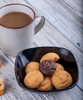 Zijaanzicht van cookies in een zwarte kom en een kopje met cacao