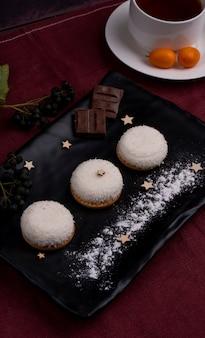 Zijaanzicht van cookies met kokos vlokken en chocoladestukjes op een zwarte bord