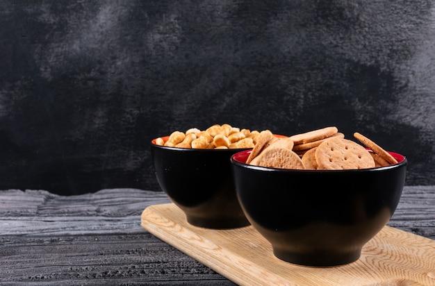 Zijaanzicht van crackers in kommen op houten scherpe raad en donkere horizontaal