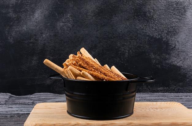 Zijaanzicht van crackers in zwarte pan en houten scherpe raad op donkere horizontaal