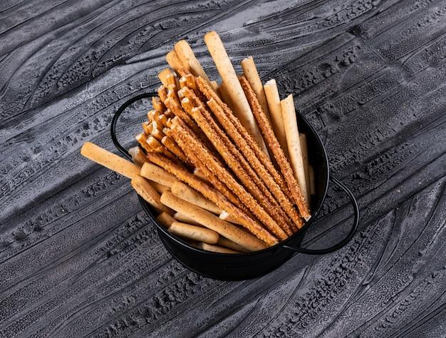 Zijaanzicht van crackers in zwarte pan op donkere horizontaal