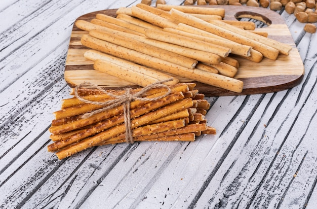 Zijaanzicht van crackers op houten scherpe raad op wit horizontaal
