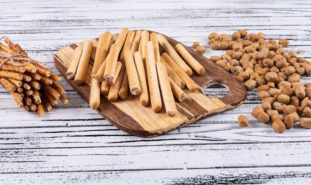 Zijaanzicht van crackers op scherpe raad op witte houten horizontaal