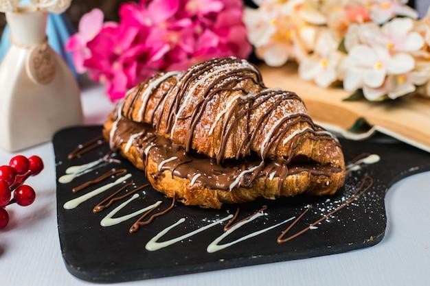 Zijaanzicht van croissant versierd met chocolade op een houten bord