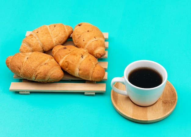 Zijaanzicht van croissants met koffie op blauwe horizontale oppervlakte