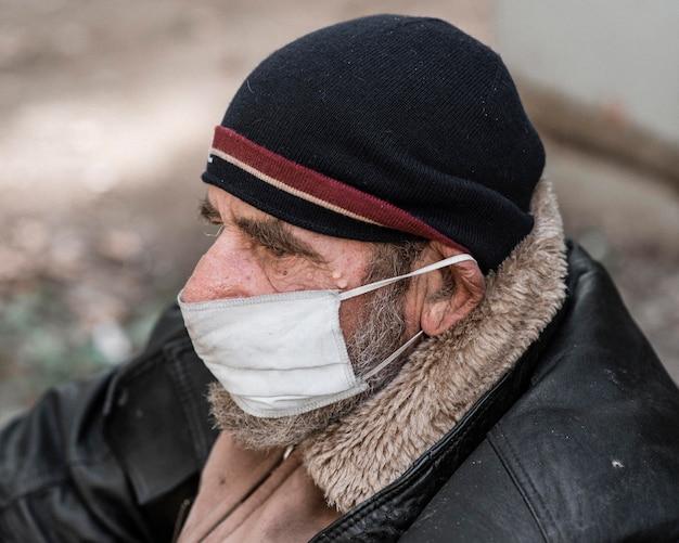 Zijaanzicht van dakloze man buitenshuis met medische masker