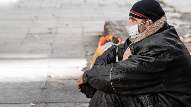 Zijaanzicht van dakloze man buitenshuis met stok en kopie ruimte