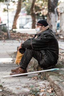 Zijaanzicht van dakloze man buitenshuis met stok en medisch masker