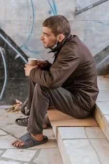 Zijaanzicht van dakloze man met kopje op trappen