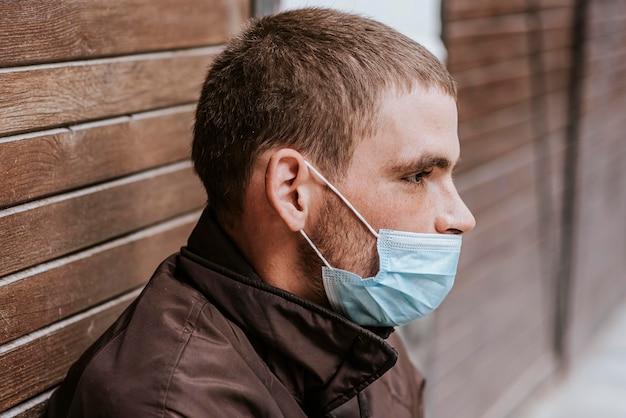 Zijaanzicht van dakloze man op straat met medisch masker