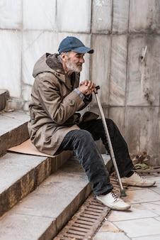 Zijaanzicht van dakloze man op trappen met stok