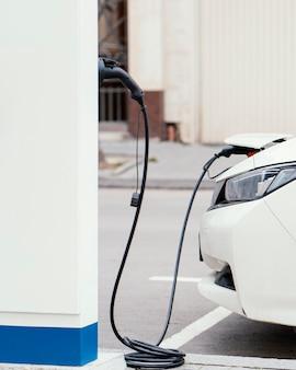 Zijaanzicht van de auto die wordt opgeladen bij het laadstation voor elektrische voertuigen