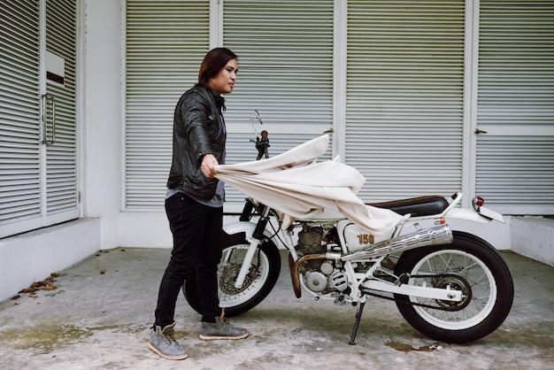 Zijaanzicht van de aziatische mens die paraplu op zijn fiets zet