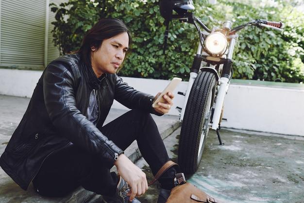 Zijaanzicht van de aziatische mens in leerjasje sittibg bij de motorfiets met smartphone in openlucht