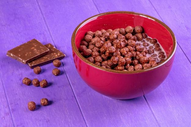 Zijaanzicht van de ballen van het chocoladegraangewas met melk in een kom en donkere chocolade op purpere houten achtergrond