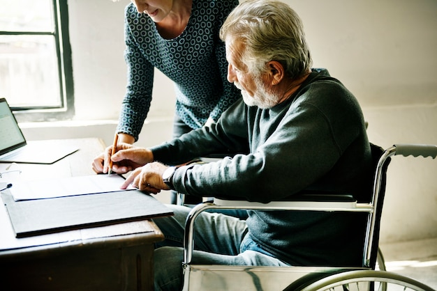 Zijaanzicht van de bejaarde man documenten invullen