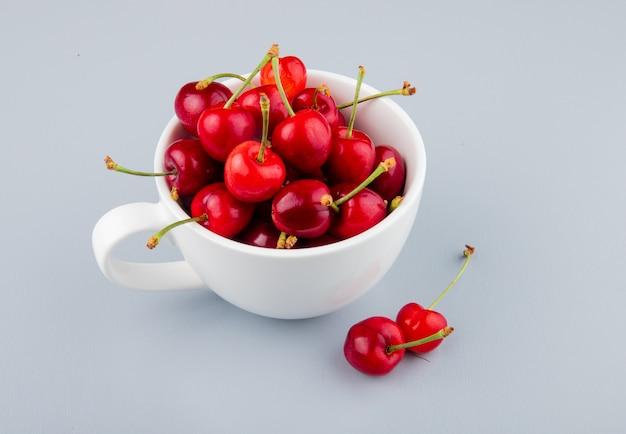 Zijaanzicht van de beker vol met rode kersen aan de linkerkant en witte tafel