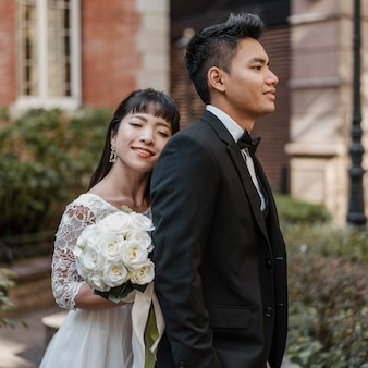 Zijaanzicht van de bruid achter bruidegom terwijl boeket