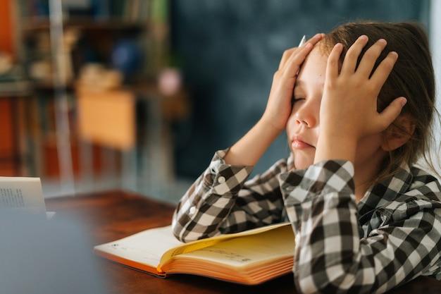 Zijaanzicht van de close-up van een verdrietig, uitgeput schoolmeisje dat moe is van het studeren met het hoofd vast