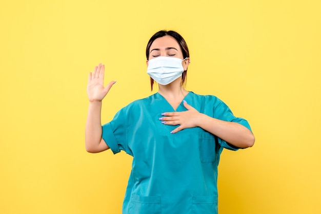 Zijaanzicht van de dokter in een masker belooft patiënten met covid te genezen