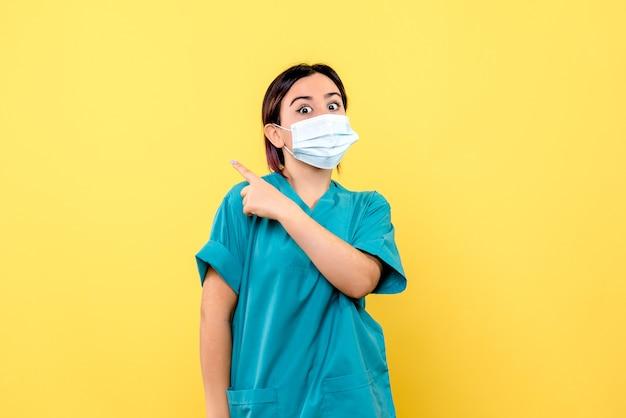 Zijaanzicht van de dokter in een masker vertelt over patiënten met covid