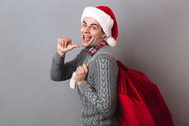 Zijaanzicht van de gelukkige man in trui en kerstmuts met tas met cadeautjes terwijl hij achteruit wijst en kijkt