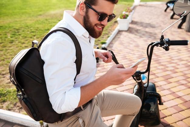 Zijaanzicht van de glimlachende gebaarde mens die in zonnebril op moderne motor in openlucht zitten en smartphone gebruiken