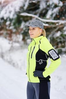 Zijaanzicht van de glimlachende vrouw die vóór het hardlopen opwarmt