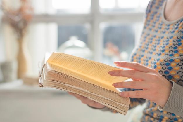 Zijaanzicht van de hand die van de jonge vrouw de pagina's van boek draait