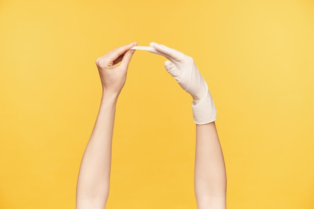 Zijaanzicht van de hand die van het jonge wijfje rubberen handschoen uit de andere hand trekt terwijl wordt geïsoleerd over oranje achtergrond. menselijke handen en gebaren concept