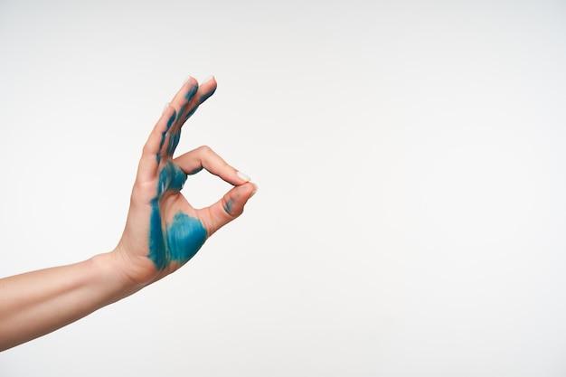 Zijaanzicht van de hand van het opgeheven jonge vrouwtje geschilderd in blauwe kleur die zich met vingers goed gedaan teken vormt terwijl ze op wit staat. tekenen en gebaren concept