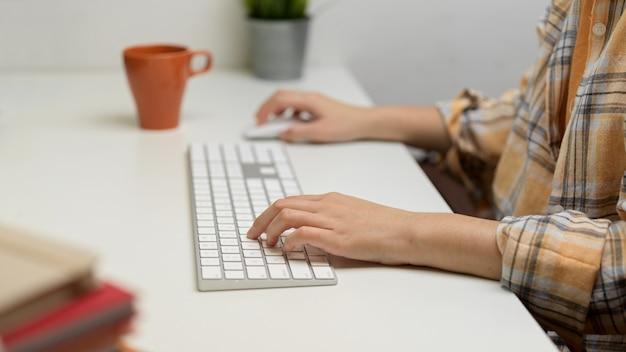 Zijaanzicht van de handen van de vrouw typen op het toetsenbord van de computer op witte tafel