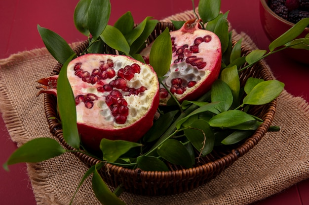Zijaanzicht van de helften van granaatappel met bladtakken in een mand op een beige servet rood oppervlak