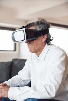 Zijaanzicht van de hogere mens die een virtuele werkelijkheidshoofdtelefoon met behulp van